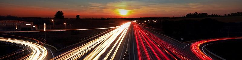 Time lapse image of a busy highway at sunset.