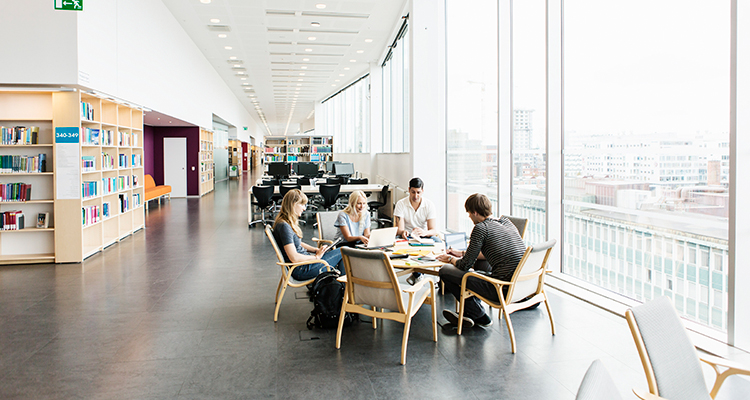 Image of college students with laptops and books working together in a modern library.