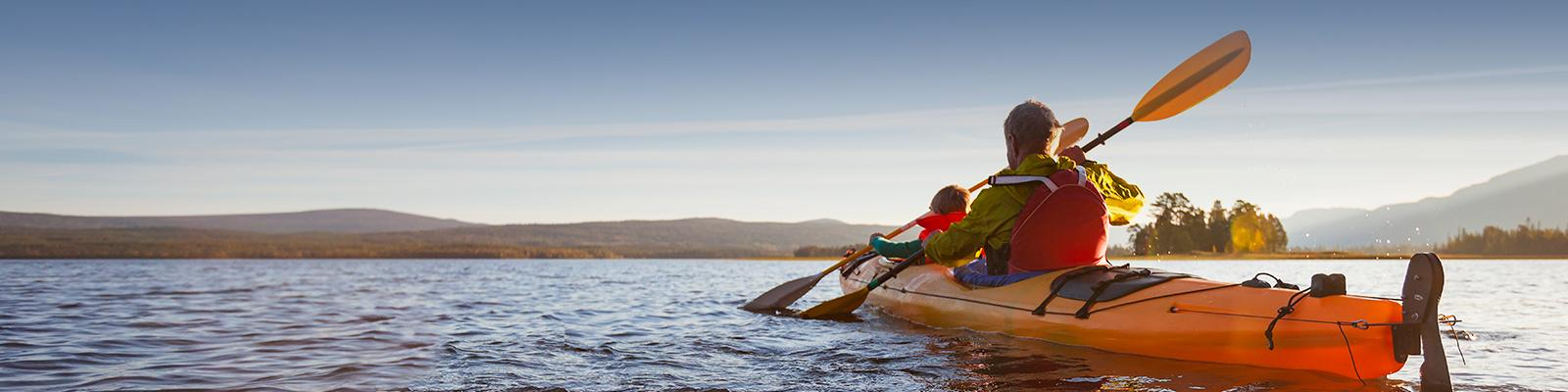 An image of adult and child kayaking on a lake.
