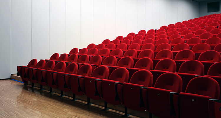 Image of unoccupied red chairs in an auditorium.